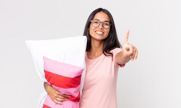Młoda latynoska kobieta uśmiechnięta i wyglądająca przyjaźnie, pokazująca numer jeden w piżamie i trzymająca poduszkę