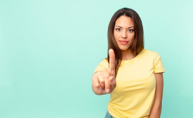 Młoda latynoska kobieta uśmiechnięta i wyglądająca przyjaźnie, pokazująca numer jeden
