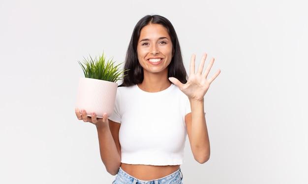 Młoda latynoska kobieta uśmiechnięta i wyglądająca przyjaźnie, pokazująca numer pięć i trzymająca ozdobną roślinę domową
