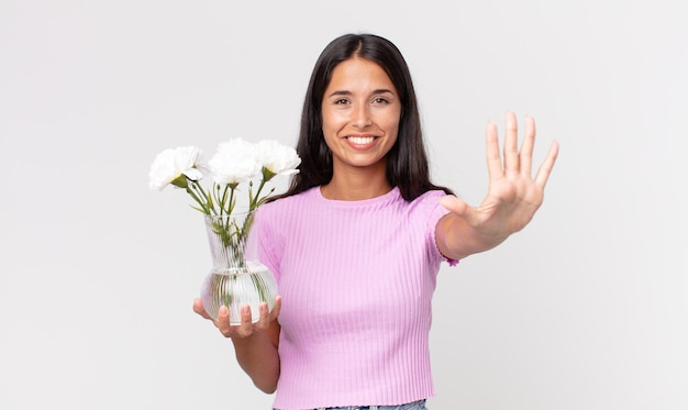 Młoda latynoska kobieta uśmiechnięta i wyglądająca przyjaźnie, pokazująca numer pięć trzymająca ozdobne kwiaty