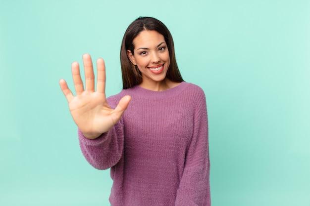 Młoda latynoska kobieta uśmiechnięta i wyglądająca przyjaźnie, pokazująca numer pięć