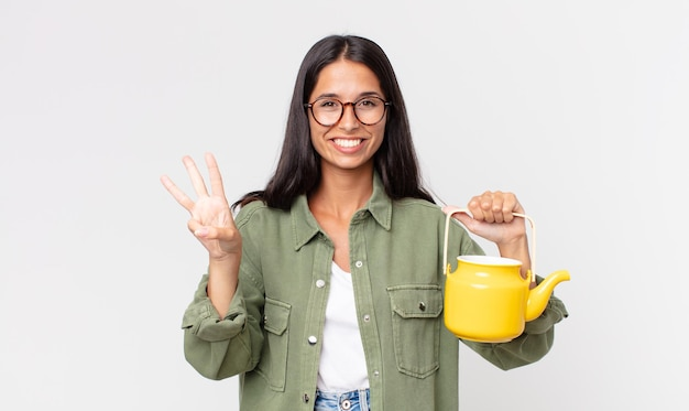Młoda latynoska kobieta uśmiechnięta i wyglądająca przyjaźnie, pokazująca numer trzy i trzymająca dzbanek do herbaty