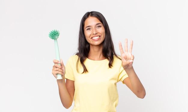 Młoda latynoska kobieta uśmiechnięta i wyglądająca przyjaźnie, pokazująca numer trzy i trzymająca szczoteczkę do mycia naczyń