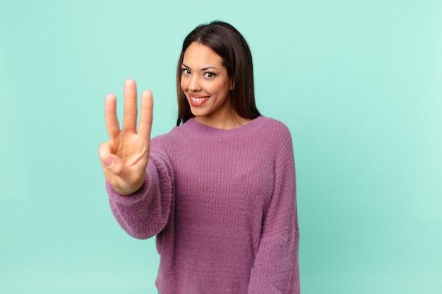 Młoda latynoska kobieta uśmiechnięta i wyglądająca przyjaźnie, pokazująca numer trzy