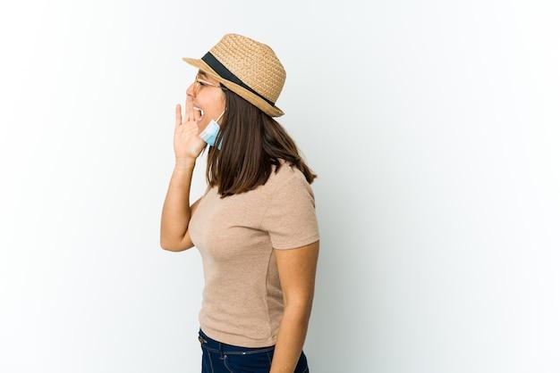 Młoda latynoska kobieta w kapeluszu i masce, aby chronić przed covid na białej ścianie, krzyczy i trzyma dłoń w pobliżu otwartych ust.