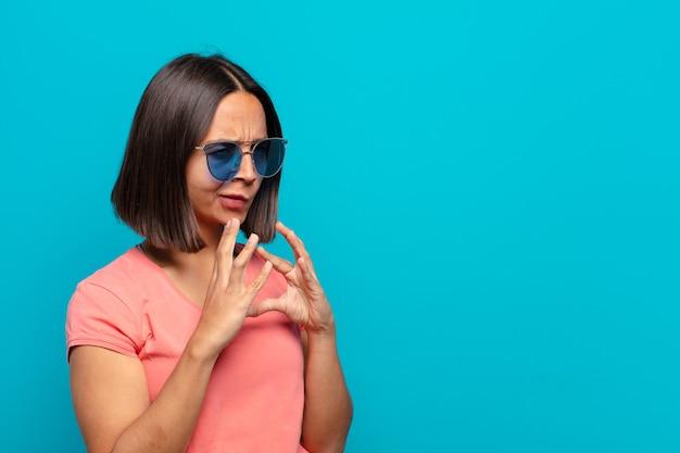 Młoda latynoska kobieta w okularach przeciwsłonecznych i przestrzeni kopii