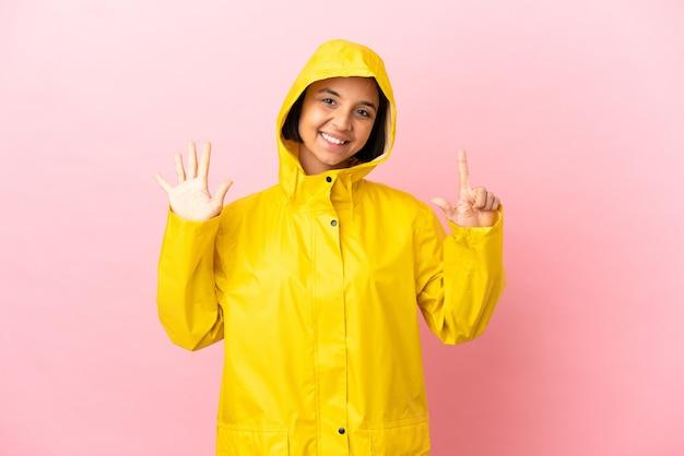 Młoda latynoska kobieta w płaszczu przeciwdeszczowym na białym tle, licząc siedem palcami