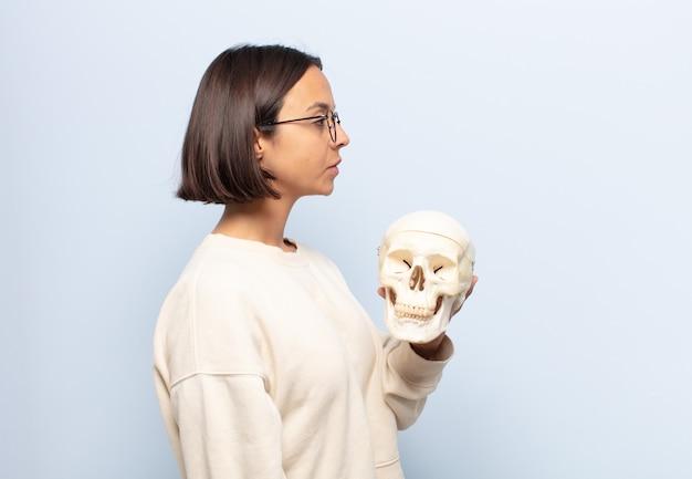 Młoda latynoska kobieta w widoku profilu chce skopiować przestrzeń do przodu, myśleć, wyobrażać sobie lub marzyć