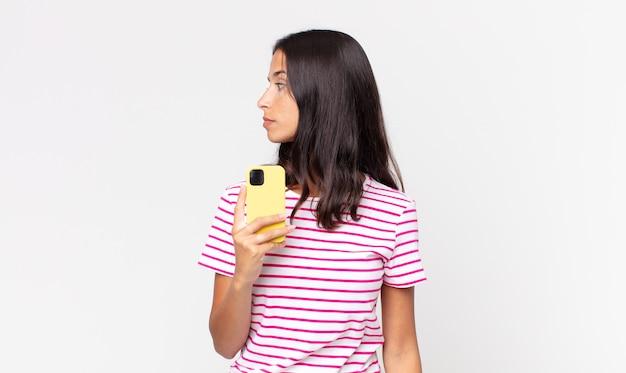 Młoda latynoska kobieta w widoku profilu myśląca, wyobrażająca sobie lub marząca na jawie i trzymająca smartfona