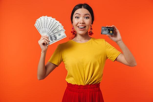 Młoda latynoska kobieta w wieku 20 lat ubrana w spódnicę, uśmiechnięta, trzymająca gotówkę i kartę kredytową na białym tle nad czerwoną ścianą