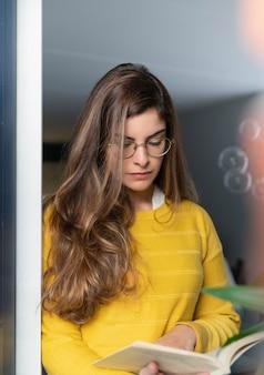 Młoda latynoska kobieta w żółtej koszuli stojąca przy oknie i czytająca książkę