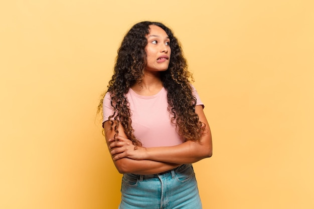 Młoda latynoska kobieta wątpi lub myśli, przygryza wargę i czuje się niepewnie i nerwowo, chcąc skopiować przestrzeń z boku
