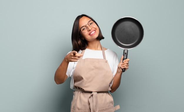 Młoda latynoska kobieta wskazująca na aparat z zadowolonym, pewnym siebie, przyjaznym uśmiechem, wybierająca ciebie