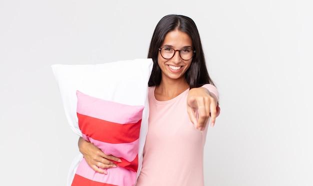 Młoda latynoska kobieta wskazująca na kamerę, która wybiera cię w piżamie i trzyma poduszkę