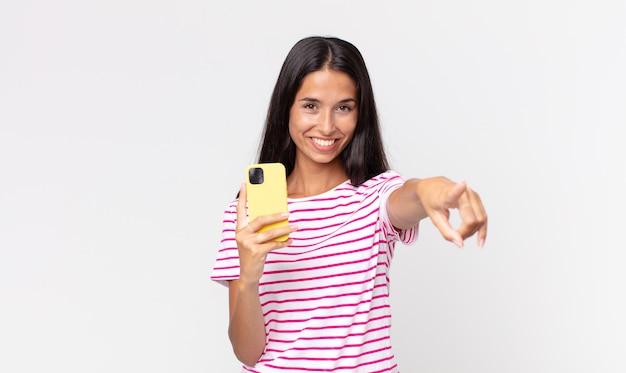 Młoda latynoska kobieta wskazująca na kamerę, wybierająca cię i trzymająca smartfona