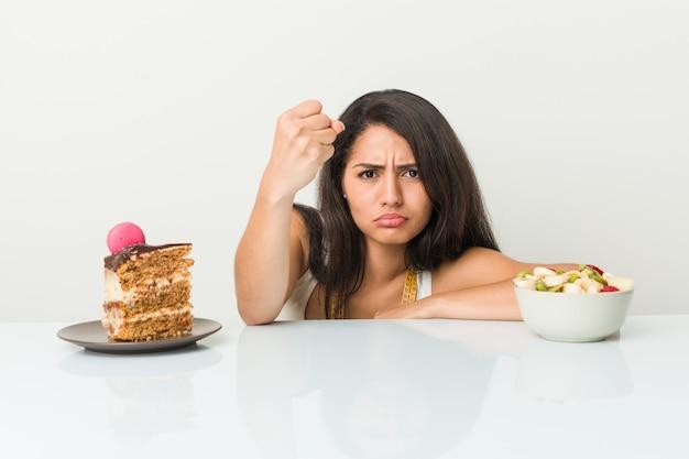 Młoda latynoska kobieta wybiera między tortem lub owoc w agresywnym wyrazie twarzy.