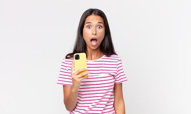 Młoda latynoska kobieta wygląda na bardzo zszokowaną lub zaskoczoną i trzyma smartfon