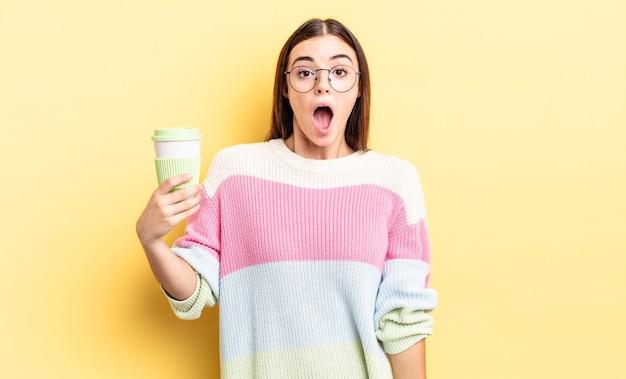 Młoda latynoska kobieta wygląda na bardzo zszokowaną lub zdziwioną. koncepcja kawy na wynos