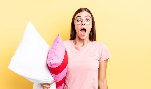 Młoda latynoska kobieta wygląda na bardzo zszokowaną lub zdziwioną. koncepcja piżamy i poduszki