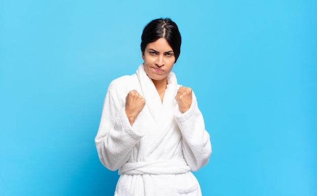 Młoda latynoska kobieta wygląda na pewną siebie, złą, silną i agresywną, z pięściami gotowymi do walki w pozycji bokserskiej. koncepcja szlafrok