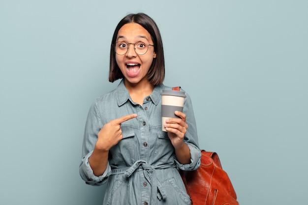Młoda latynoska kobieta wygląda na podekscytowaną i zaskoczoną, wskazując na bok i w górę, aby skopiować przestrzeń
