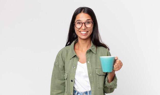 Młoda latynoska kobieta wygląda na szczęśliwą i mile zaskoczoną, trzymając kubek z kawą