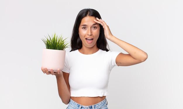 Młoda latynoska kobieta wygląda na szczęśliwą, zdumioną i zaskoczoną i trzyma ozdobną roślinę domową