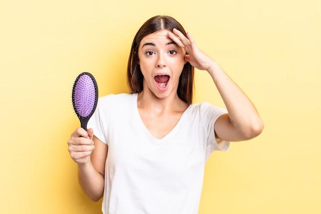 Młoda latynoska kobieta wygląda na szczęśliwą, zdumioną i zdziwioną. koncepcja szczotki do włosów