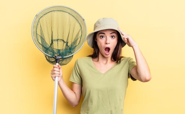 Młoda latynoska kobieta wygląda na zaskoczoną, realizując nową myśl, pomysł lub koncepcję koncepcji sieci rybackiej