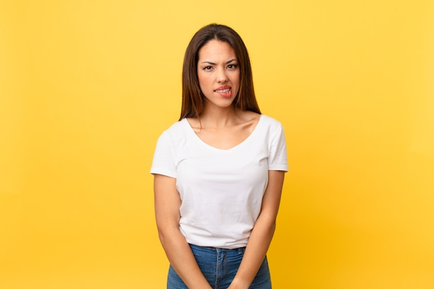 Młoda latynoska kobieta wygląda na zdziwioną i zdezorientowaną