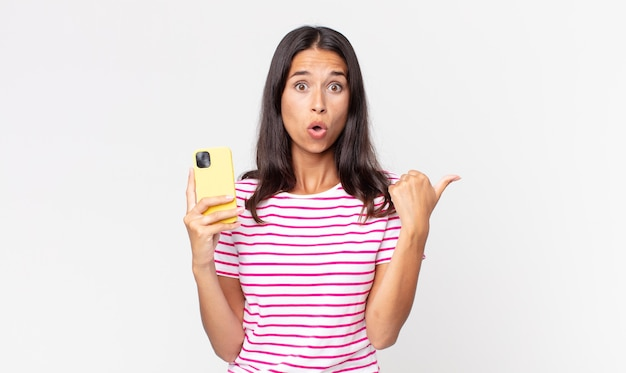 Młoda latynoska kobieta wygląda na zdziwioną z niedowierzaniem i trzyma smartfon