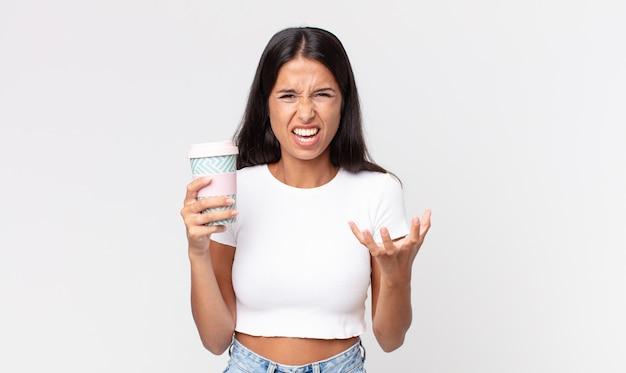 Młoda latynoska kobieta wygląda na złą, zirytowaną i sfrustrowaną i trzyma pojemnik na kawę na wynos