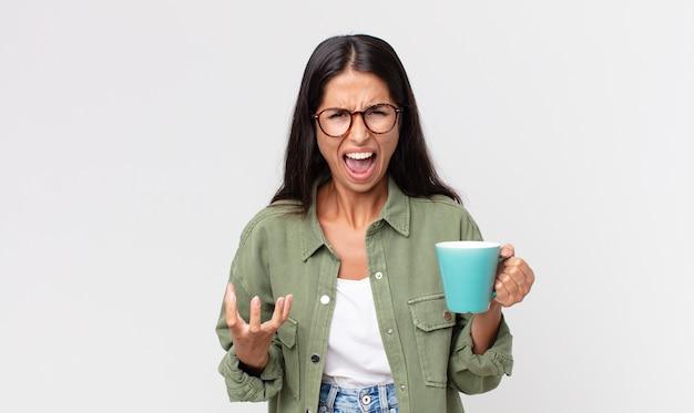 Młoda latynoska kobieta wygląda na złą, zirytowaną i sfrustrowaną, trzymając kubek z kawą