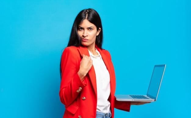 Młoda latynoska kobieta wyglądająca na arogancką, odnoszącą sukcesy, pozytywną i dumną, wskazującą na siebie. koncepcja laptopa