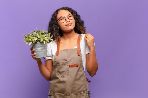 Młoda latynoska kobieta wyglądająca na arogancką, odnoszącą sukcesy, pozytywną i dumną, wskazującą na siebie. koncepcja opiekuna ogrodu