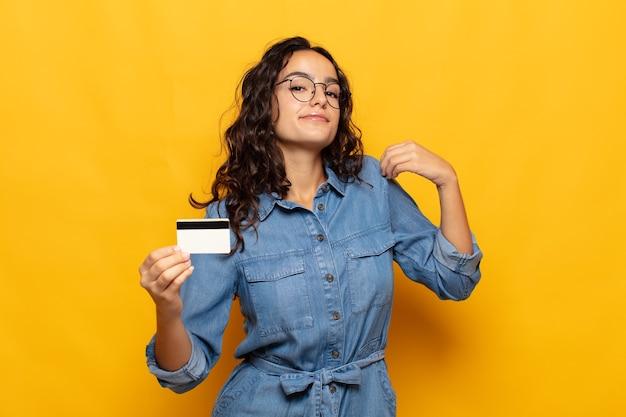 Młoda latynoska kobieta wyglądająca na arogancką, odnoszącą sukcesy, pozytywną i dumną, wskazującą na siebie
