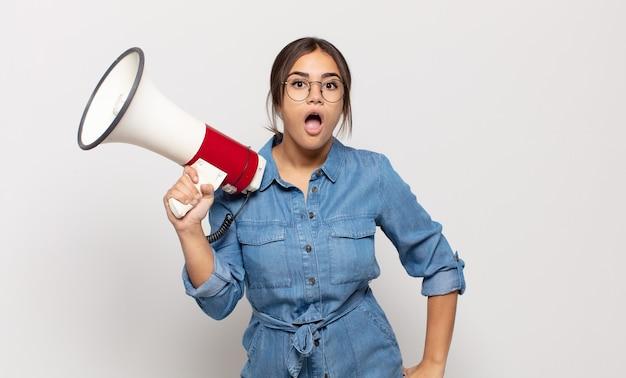 Młoda latynoska kobieta wyglądająca na bardzo zszokowaną lub zaskoczoną, patrząc z otwartymi ustami i mówiącą wow