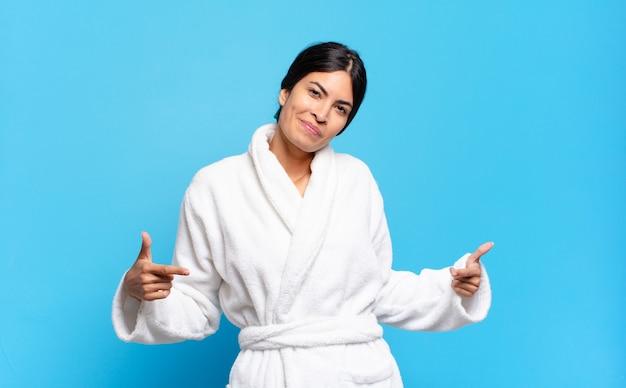 Młoda latynoska kobieta wyglądająca na dumną, arogancką, szczęśliwą, zaskoczoną i usatysfakcjonowaną, wskazującą na siebie, czującą się jak zwycięzca. koncepcja szlafrok