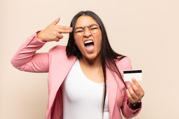 Młoda latynoska kobieta wyglądająca na niezadowoloną i zestresowaną, samobójczy gest wykonujący znak pistoletu ręką, wskazujący na głowę