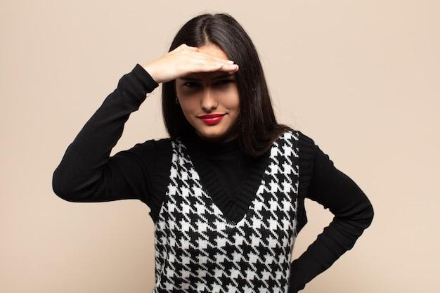 Młoda latynoska kobieta wyglądająca na oszołomioną i zdumioną, z ręką na czole spoglądającą w dal, obserwującą lub poszukującą