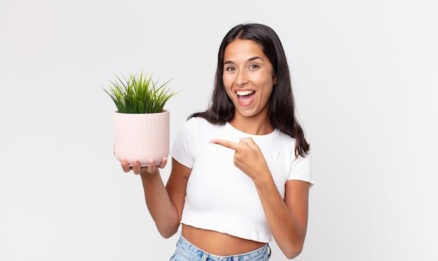 Młoda latynoska kobieta wyglądająca na podekscytowaną i zaskoczoną, wskazując na bok i trzymająca ozdobną roślinę domową