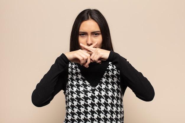 Młoda latynoska kobieta wyglądająca na poważną i niezadowoloną z dwoma palcami skrzyżowanymi do góry w odrzuceniu, proszącą o ciszę