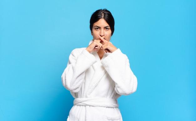 Młoda latynoska kobieta wyglądająca na poważną i niezadowoloną, z dwoma palcami skrzyżowanymi z przodu w odrzuceniu, prosząc o ciszę. koncepcja szlafrok