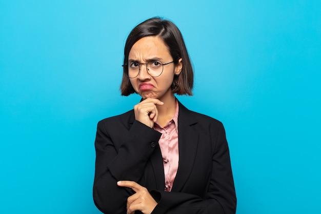 Młoda latynoska kobieta wyglądająca na poważną, zdezorientowaną, niepewną i zamyśloną, wątpiącą w opcje lub wybory