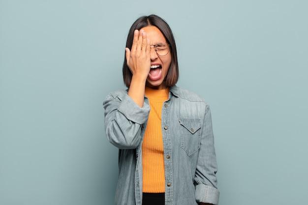 Młoda latynoska kobieta wyglądająca na śpiącą, znudzoną i ziewającą, z bólem głowy i jedną ręką zakrywającą połowę twarzy