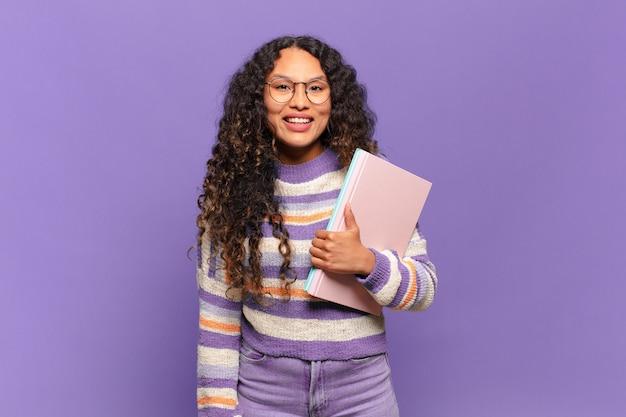 Młoda latynoska kobieta wyglądająca na szczęśliwą i mile zaskoczoną, podekscytowaną z wyrazem fascynacji i szoku. koncepcja studenta