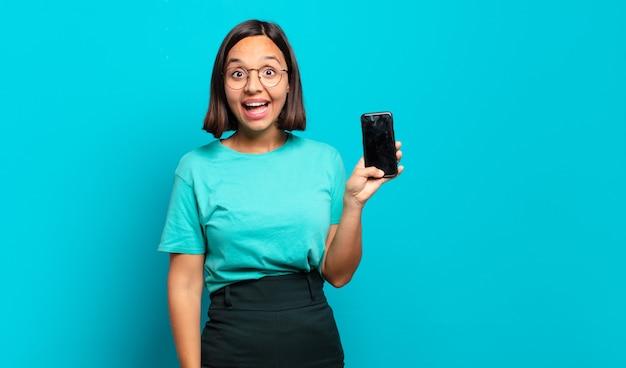 Młoda latynoska kobieta wyglądająca na szczęśliwą i mile zaskoczoną, podekscytowaną zafascynowaną i zszokowaną miną