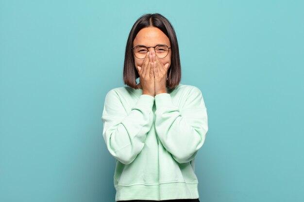 Młoda latynoska kobieta wyglądająca na szczęśliwą, wesołą, szczęśliwą i zdziwioną zakrywającą usta obiema rękami