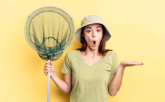 Młoda latynoska kobieta wyglądająca na zaskoczoną i zszokowaną, z opuszczoną szczęką, trzymającą koncepcję sieci na ryby