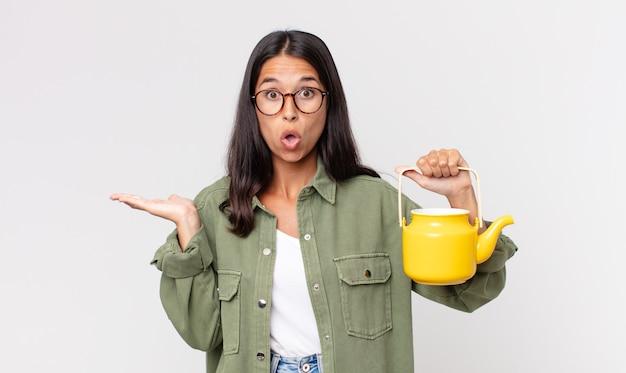 Młoda latynoska kobieta wyglądająca na zaskoczoną i zszokowaną, z opuszczoną szczęką, trzymająca przedmiot i trzymająca dzbanek na herbatę
